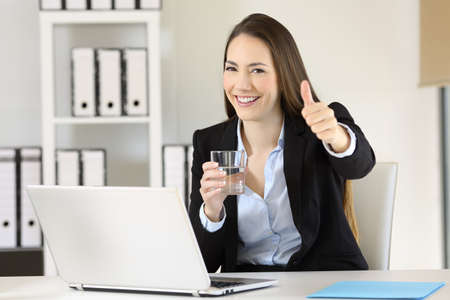 Portrait of an office worker holding a glass of water looking at you sitting in a desktop