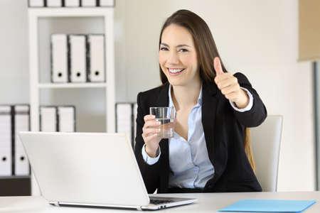 Retrato de un oficinista que sostiene un vaso de agua mirándote sentado en un escritorio Foto de archivo - 93402910