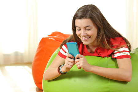 Teen using a blue smart phone lying on a colorful pouff at home