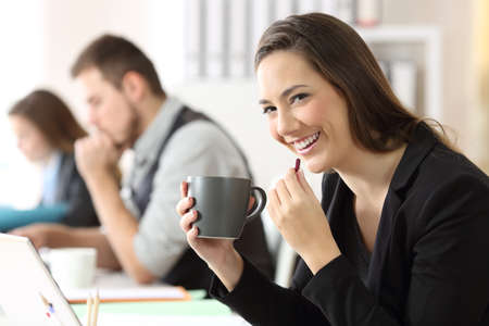 Happy businesswoman taking a pill and looking at camera at office Stock Photo