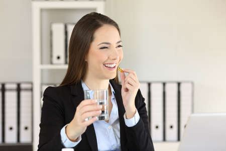 Smiley businesswoman taking a pill and holding a glass of water at office