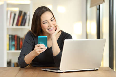 Front view portrait of a happy girl using a blue smart phone and laptop on a table at home
