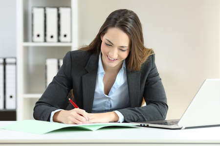 Front view portrait of an executive signing a document on a desktop at office
