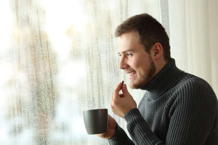 Side view portrait of a happy man taking a pill looking through a window in a rayny day of winter at home Stock Photo