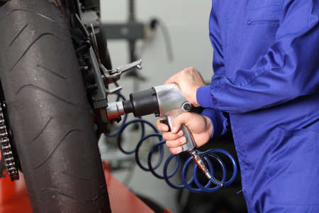 Close up of a motorcycle mechanic hands working usinb a pneumatic gun to thighten a nut in a mechanical workshop Archivio Fotografico