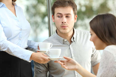Disloyal boyfriend looking at breast of a waiter in front of his distracted girlfriend Foto de archivo