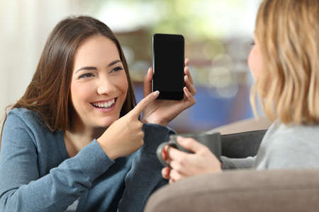Happy girl showing a blank phone screen to a friend on a couch at home