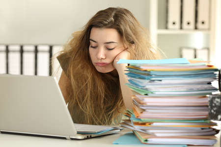 Exhausted intern with tousled hair working hard reading a lot of documents at office Stock Photo