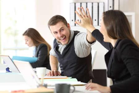 Twee opgewekte collega's die prestatie vieren die vijf geven op kantoor