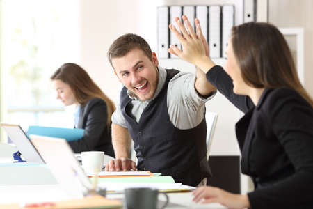 Two excited coworkers celebrating achievement giving five at office Stock Photo