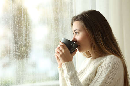 Side view portrait of a relaxed teen drinking coffee looking outside through a window in a rainy day of winter at home