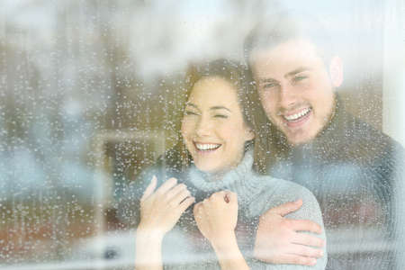 Front view portrait of a joyful couple looking through a window in a rainy day at home
