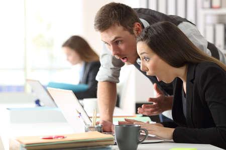 Dwa zdziwionego współpracownika czyta on-line wiadomość w laptopie przy biurem Zdjęcie Seryjne