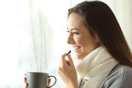 Zijaanzichtportret van een gelukkige vrouw die een pil neemt en door een venster in een regenachtige dag van de winter kijkt Stockfoto - 93881808