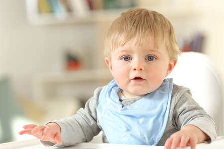 Front view portrait of a relaxed cute baby ready to eat looking at camera on a high chair at home Foto de archivo