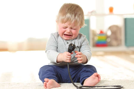 Front view portrait of a baby aby in danger crying holding an an electric plug sitting on the floor at home Stockfoto