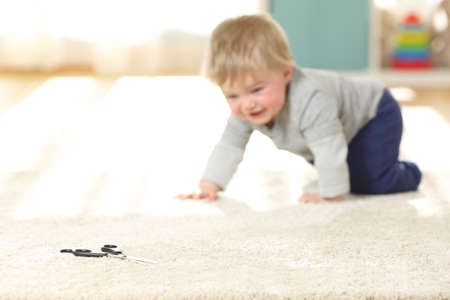 Baby in danger crawling towards a scissors on a carpet at home Stok Fotoğraf