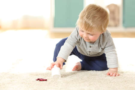 Baby in danger playing with a bottle of pills on the floor at home Stock Photo - 93881810