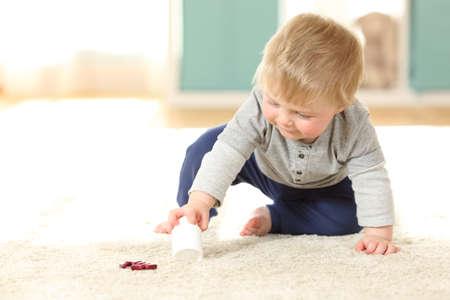 Baby in gevaar het spelen met een fles pillen op de vloer thuis Stockfoto - 93881810