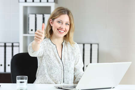 Satisfied office employee looking at camera with thumbs up
