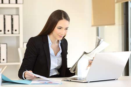 Oficinista serio que compara contenido en línea con un periódico y documentos