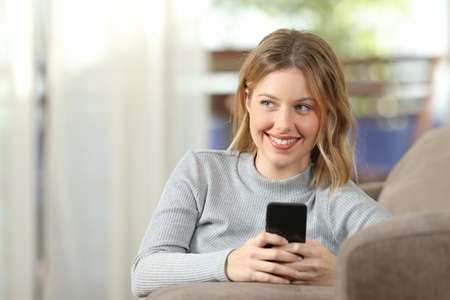 Front view portrait of a pensive blonde using a smart phone on a couch at home Stock Photo