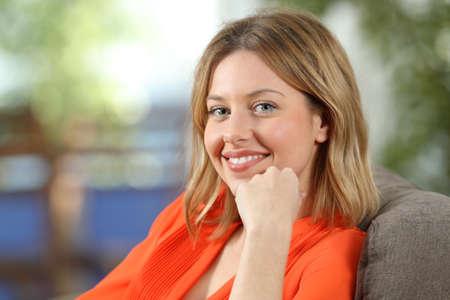 自宅のソファに座ってカメラを見てオレンジ色の幸せなブロンドの女性の肖像画 写真素材 - 93964033