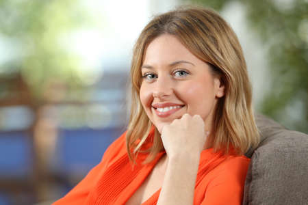 Portrait of a happy blonde woman in orange looking at camera sitting on a couch at home