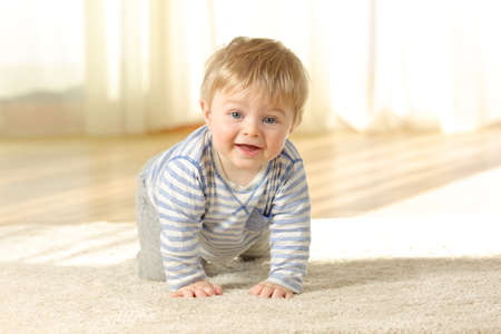 Happy baby crawling towards camera and looking at you on a carpet at home Stok Fotoğraf