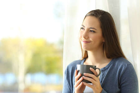 Portrait of a satisfied woman thinking looking at side holding a coffee mug beside a window at home