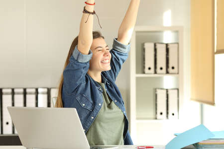Portrait of a young satisfied intern raising arms at office Banque d'images
