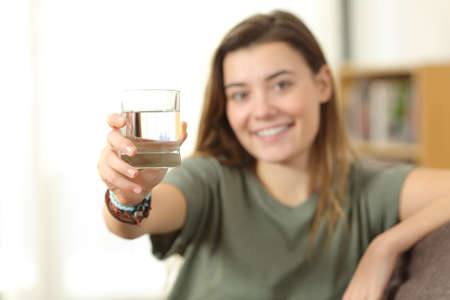 Healthy teen showing a glass of water sitting on a couch at home Foto de archivo - 93964038