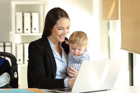 Happy mother working on line with a laptop holding her baby son at office