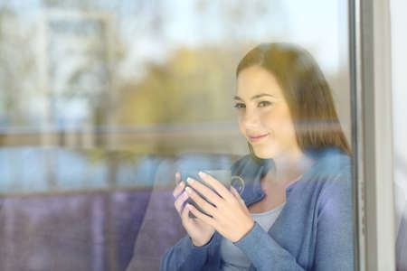 Serious woman looking forward through a window at home with outside reflections on the glass Stock Photo