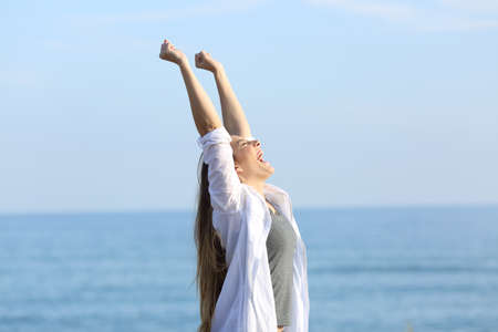 Retrato de vista lateral de uma mulher excitada, gritando e levantando os braços na praia com o mar ao fundo