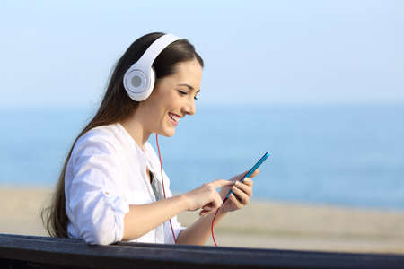 Side view portrait of a happy woman listening to music wearing headphones sitting on a bench on the beach