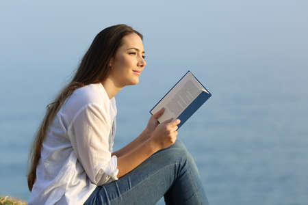 Portrait of a happy woman dreaming and reading a book looking away on the beach