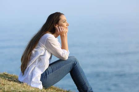 背景の海を見て草の上に座ってリラックス幸せな女性のサイドビューの肖像画