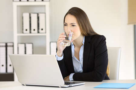 Serious businesswoman drinking healthy fresh water at office Stock Photo