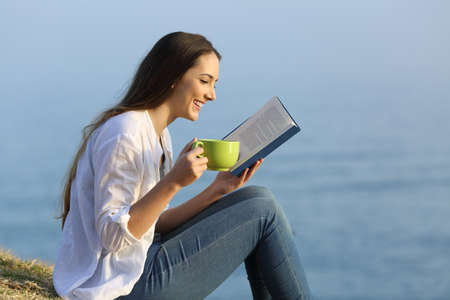 Side view portrait of a happy girl relaxing reading a book and drinking coffee sitting on the grass on the beach