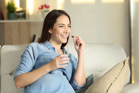 Portrait of a happy pregnant woman taking a pill sitting on a couch in the living room at home