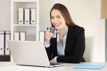 Executivo feliz segurando um copo de água e olhando para a câmera no escritório Foto de archivo - 94372930