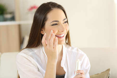 Portrait of a beauty woman applying moisturizer cream on the face sitting on a couch in the living room at home Stock Photo