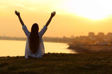 Retrato de backlight vista traseira de uma mulher solteira feliz, vendo a cidade ao pôr do sol e levantando os braços com uma luz quente no fundo