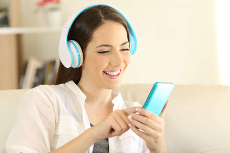 Happy girl listening to music and choosing a song in a smart phone sitting on a couch in the living room at home