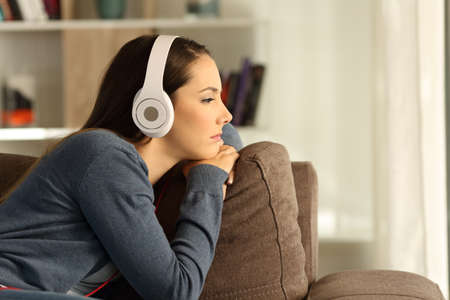 Side view portrait of a sad pensive woman listening to music sitting on a couch in the living room at home Stok Fotoğraf