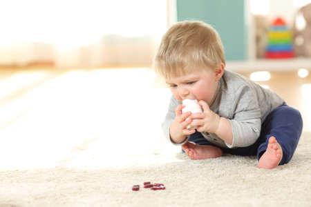 自宅の床に薬のボトルで遊んで危険にさらされている赤ちゃん