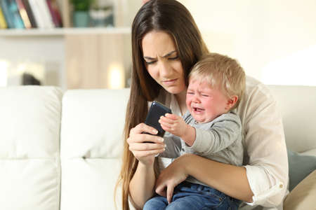 Baby having a tantrum and fighting with his mother for a smart phone sitting on a couch in the living room at home