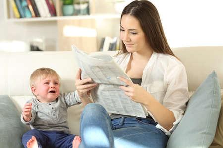 Baby huilt veeleisende aandacht en zijn moeder negeert hem zittend op een bank in de woonkamer thuis