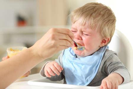 Cerca de una mano de madre alimentando a su hijo que está llorando sentado en una silla alta Foto de archivo - 94801023